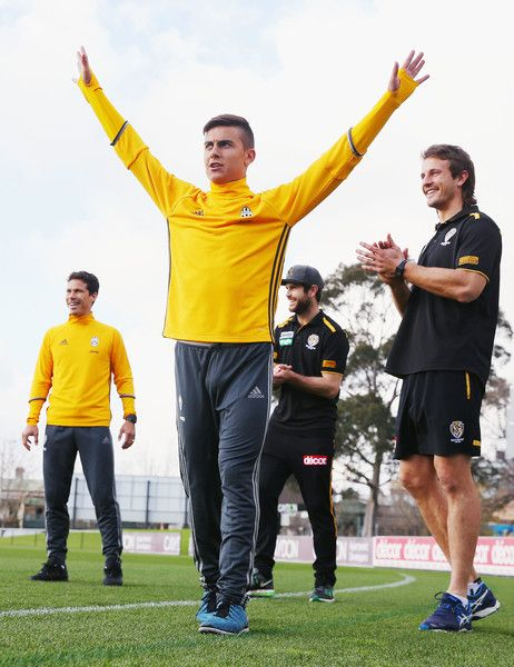 Trent Cotchin and Ivan Maric of the Tigers (R) react with Hernanes (L) as his teammate Paulo Dybala of Juventus celebrates kicking a goal during a Richmond Tigers AFL and Juventus FC media opportunity at Punt Road Oval on July 20, 2016 in Melbourne, Australia.
