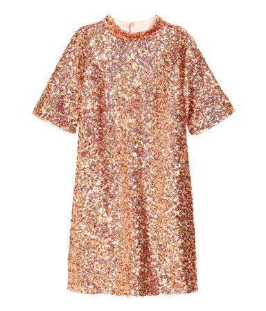 Pronssi. Suoramallinen lyhyt mekko paljettikirjailtua meshiä. Lyhyet hihat ja matala pystykaulus, jossa painonapitus niskassa. Selkäpuoli syvään uurrettu.