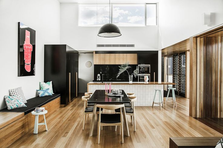 """The open-plan kitchen, dining and living space showcases a strong palette of black, white and timber tones, a soaring ceiling and copious amounts of natural light. """"We were after a really dramatic kitchen,"""" says Laura.   **Joinery** by [T&T Cabinets](http://www.ttcabinets.com.au/?utm_campaign=supplier/