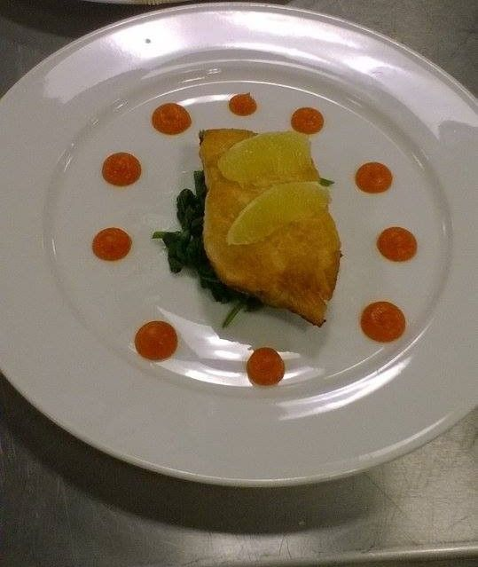 Pan fried salmon on a bed of fresh spinach with lemon segments and carrot puree to garnish