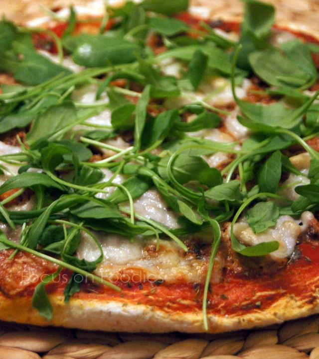 200 gram zelfrijzend glutenvrij bakmeel (Orgran Pizza & Pastry Mix, de Tuinen  40 ml water Snufje zout Tomaten saus (Passata di Pomodoro van AH) Blikje tonijn in olijfolie Verse rucola Geraspte of plakjes geitenkaas Gedroogde oregano en basilicum