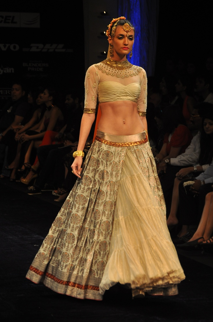 Ivory brocade lehenga with a net blouse with an orange dupatta.