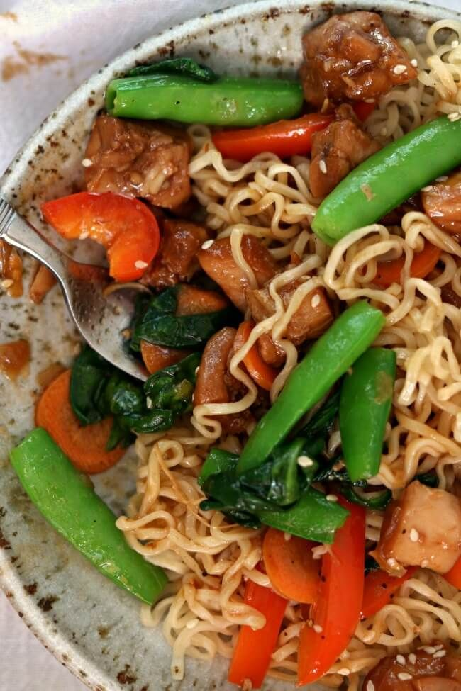 Instant Pot Honey Bourbon Chicken Noodle Bowls--tender bites of chicken thighs are cooked in a honey-soy-garlic sauce and then served over ramen-style noodles with stir fried vegetables. This chicken is just as good as what you'd order in a restaurant.