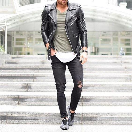 Acheter la tenue sur Lookastic: https://lookastic.fr/mode-homme/tenues/veste-motard-noir-t-shirt-a-col-en-v-olive-jean-skinny-noir/18387 — T-shirt à col en v olive — Veste motard en cuir noir — Jean skinny déchiré noir — Chaussures de sport grises