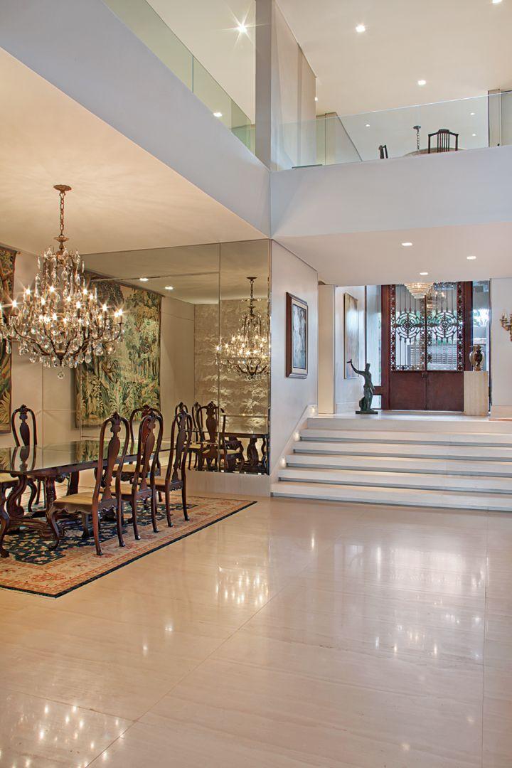 A imponente porta antiga em aço corten se destaca no hall de entrada revestido com Limestone Crema Europa. No jantar, o destaque é o grande lustre de cristais duplicado pela parede espelhada. Todo o piso do social é em mármore Travertino Romano.