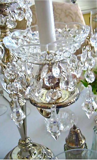 Reflective silver 14-inch, 5-branch candelabra dripping with crystal bobeches grace the center of the table.