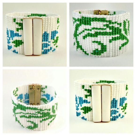 Bracelete Miçangas Floral   Trançado manualmente, com miçangas de primeira linha, nas cores Branco, Verde e Azul céu.  O fecho é com imã, revestido de textura Branca.  Dimensões:  Largura - 18,5 centímetros  Altura: 4 cm
