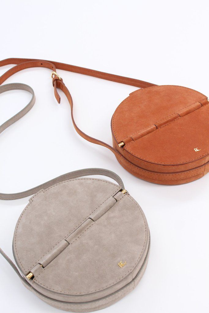 Round cross-body bag in 100% suede leather. Magnetic closure and adjustable strap. Available in grey or melon.