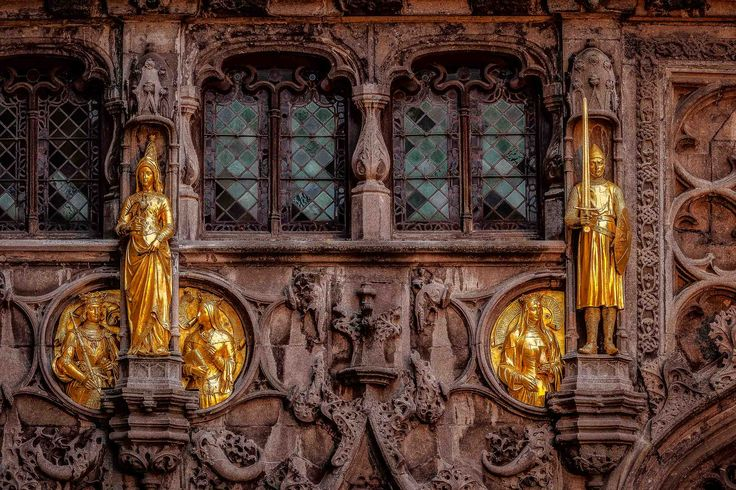 Gold colored figures decorate the facade of this building in Bruges, Belgium.