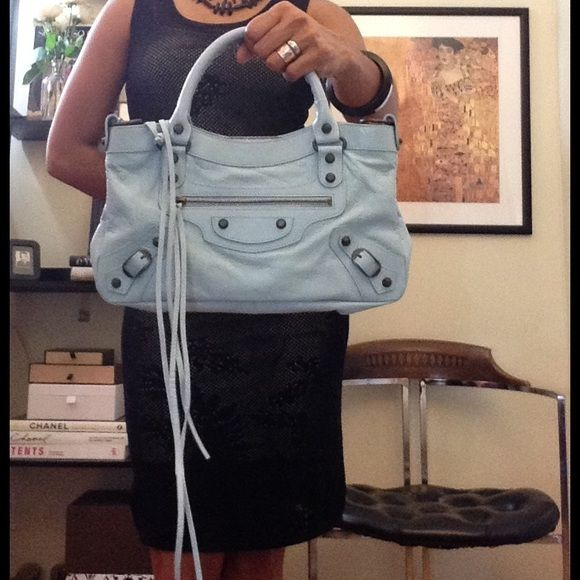 "SOLD💧Balenciaga Bleu Dragee Arena Classic Balenciaga Bleu Dragee Arena Classic First bag      -Styled with aged brasstone hardware.      -Zip pocket and metal buckles and studs at front      -Lined with fabric; two slip pockets and one zip pocket at interior      -Whipstitched rolled leather top handles; detachable flat leather shoulder strap with shoulder rest      -Top zip closure      -4.25"" handle drop, 7"" strap drop      -Includes leather-bound travel mirror      -Made in Italy…"