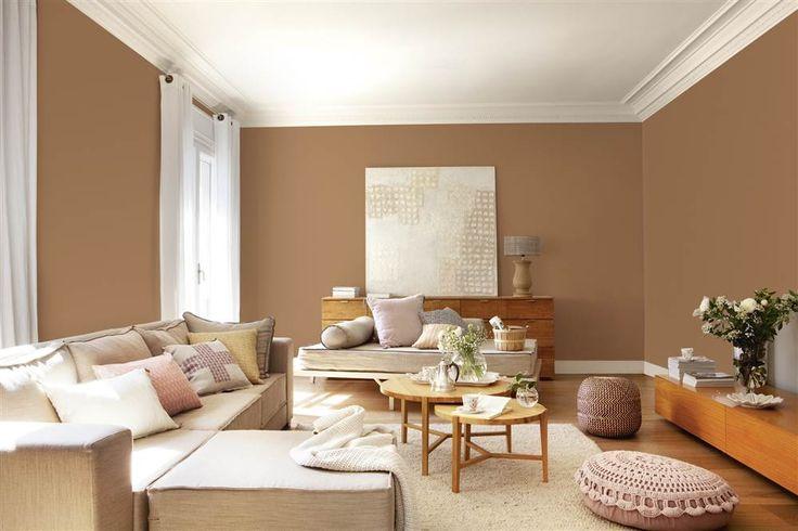 Salón con paredes marrones y techo blanco, sofá con chaise longue, mesas de centro nido redondas, pufs rosas y mueble vintage con cuadro