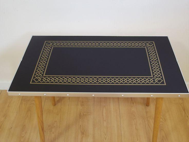 Stolik z czarnym, szklanym blatem ze złotym zdobieniem. Pochodzi z lat 70.Boczne okucia są oryginalne,…