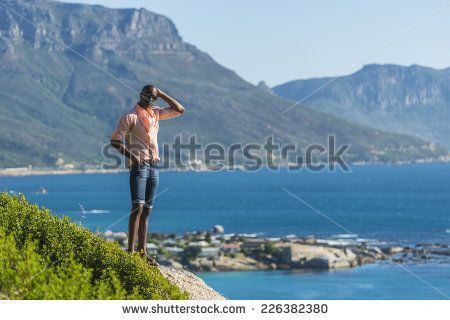 http://www.shutterstock.com/pic-226382380/stock-photo-african-black-man-standing-on-a-high-rock-overlooking-cape-town-as-he-points-and-scouts-the-blue.html?src=WuffEuvvGWj02MQSGcnIHQ-1-18 African Black Man, Standing On A High Rock Overlooking Cape Town As He Points And Scouts The Blue Sky, Ocean And Mountains On A Sunny Summers Day Stock Photo 226382380 : Shutterstock