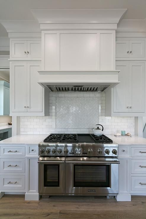 White Shaker Kitchen Cabinets Fitted With Polished Nickel Hardware And White Marble Countertops Flank A Thermador
