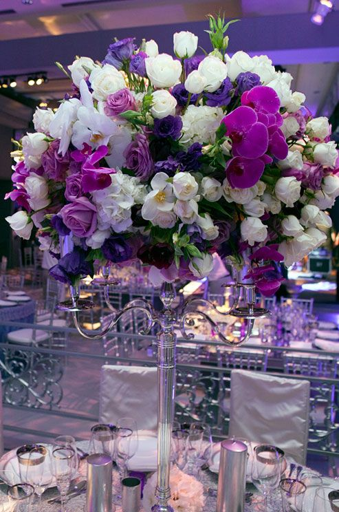 A silver candelabrum holds an arrangement of purple, white and pink roses and orchids.