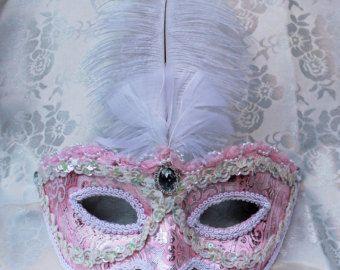 Una máscara de flor muy de fiesta para esa ocasión especial!  Cuatro tonos de papel de morera han sido aplicados sobre papel maché antes de que añadió una ligera aplicación de pegamento del brillo para sellar y proteger el papel. Entonces se han añadido un jardín lleno de flores de papel de morera rosa, marrón y multicolor. El diseño se completa con una cintas de centro de mesa y colgantes de filigrana.  La máscara mide 7 1/2 pulgadas por 3 pulgadas. Cuentan con lazos de cinta escarpada y…