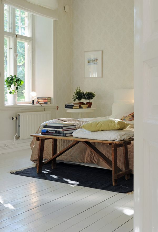 Chic wallpapered bedroom with a rustic wooden bench and fresh plants
