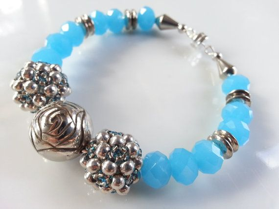Perfect for a SMALL wrist, this lovely bracelet sparkles with royal tones. Created with sky blue Chinese crystals and a variety of silver plated beads of varying shapes and sizes, the center includes two handcrafted beads of copper lined light blue Czech glass beads and silver plated beads.   Connected with a strong magnetic clasp, this artful piece is one that you will feel secure wearing for years to come. Want to present this as a Holiday ornament? Just select your ribbon option of either…