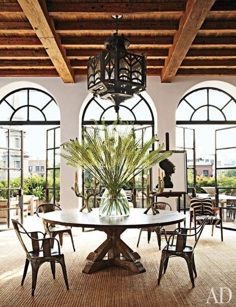 Writer Brad Goldfarb and Alfredo Paredes—executive vice president and chief retail creative officer at Ralph Lauren—collaborated with architect Michael Neumann on the renovation of their Manhattan duplex. They added double doors with arched transoms and a timber ceiling to the living/dining area, which features a table by Lucca Antiques, a suite of vintage Tolix chairs, and a Spanish wrought-iron lantern from Gustavo Olivieri. The vase is by Ralph Lauren Home, the candelabra are flea-market…
