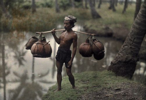 1928, Bali, Indonesia --- A Balinese man carries pots with a potent drink to be sold at market --- Image by © Franklin Price Knott/National Geographic Society/Corbis