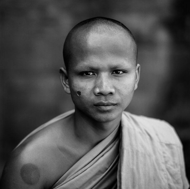 A formal portrait of a monk at the Bayon in the Angkor Wat complex near Siem Reap, Cambodia. The scare on his face is the result of being tortured, with a cigarette, by the Khmer Rouge when he was a child.