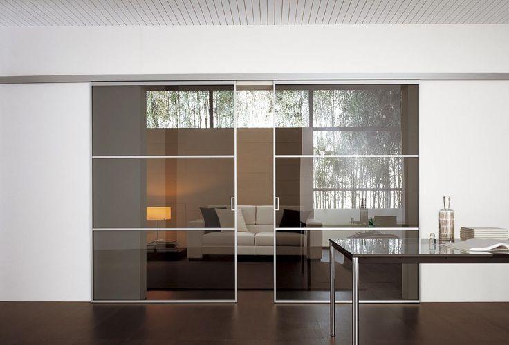 http://www.atresliving.it/porte-da-interni-a-milano/ Tra le due sale, un'ampia superficie in vetro fumé, divisa in tre settori. I percorsi in alluminio ne definiscono la geometria, mentre il binario di scorrimento è montato a parete.