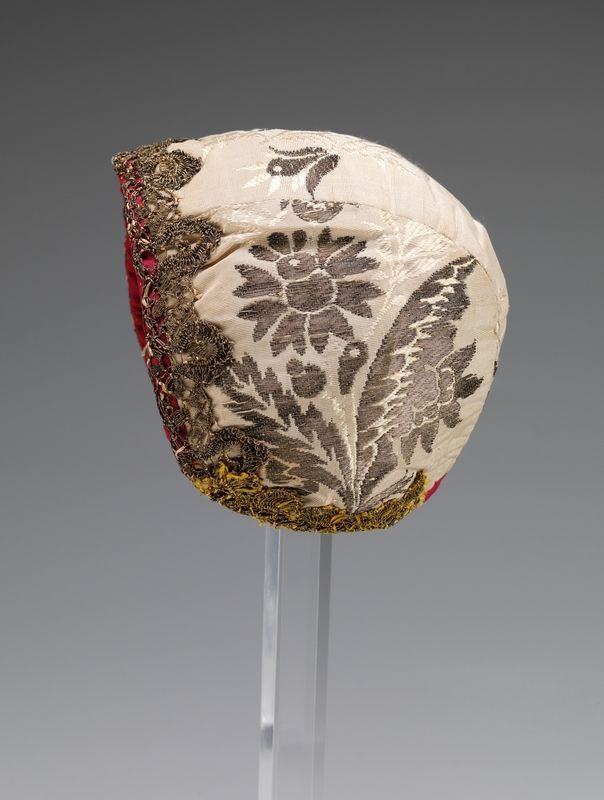 Infant's cap, Norway, mid 18th century. Cream silk brocade decorated with metallic lace.