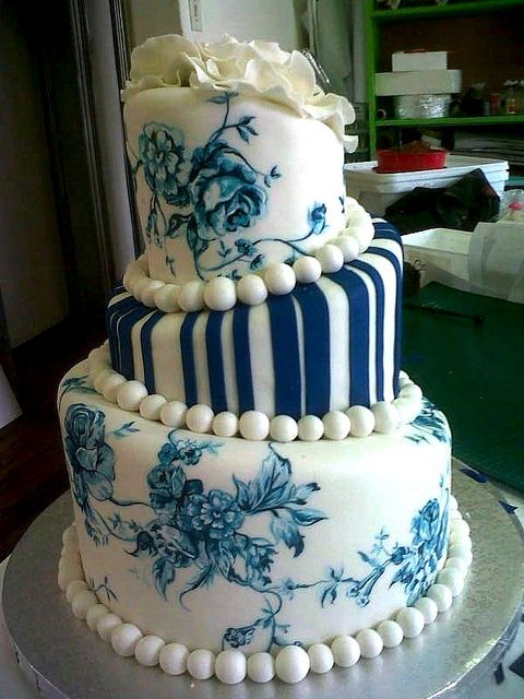 3-tier Topsy Turvy Mad Hatter wedding cake covered in white fondant icing, decorated with blue hand-painted Delft designs, blue fondant stripes & 3 white floppy fondant roses | Flickr: Intercambio de fotos