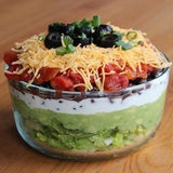 Lightened-Up 7 Layer Dip.  This looks delicious! Will be making soon!    2 cups chopped romaine lettuce  2 avocados, mashed well  1 cup low-fat Greek yogurt  2/3 cup black beans  1/2 cup diced tomatoes  1/2 cup shredded cheddar cheese  Sliced black olives and scallions to garnish    Delish!