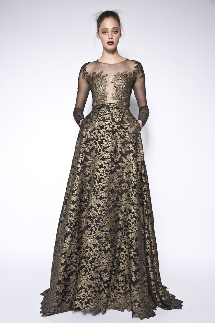 Gold coated lace embellished gown with pockets. The Avalbane Dress is made of a black mesh fabric and emblished with gold coated lace.This dress features an open deep v neckline illusion, long sheer sleeves and is designed to be fitted at the bodice and waist but then flares. The embelished details on the sleves and bodice bring the dress together and create an elegant look. #evening #embellishment #illusion #floral #lace #gold #black #sleeves #specialoccasion #pockets