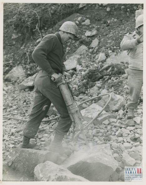 "21 Nov 44. 5/MM-44-30340. Fifth Army, South of Bologna, Italy. Pneumatic hammers are also used as well as sledge hammers, to break rock before it is used for repairing and rebuilding roads washed away by heavy rains. This soldier of the 19th Engineers of the Fifth Army is using the hammer on some of the heavier rock. Photo by Mason. 3131 Signal Service Co."" South of Bologna, Italy. 21 November 1944"