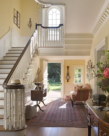 This foyer is very elegant w/ fine antiques art work,large oriental rug & gorgeous staircase.The wood work & palladium window are exquiste.