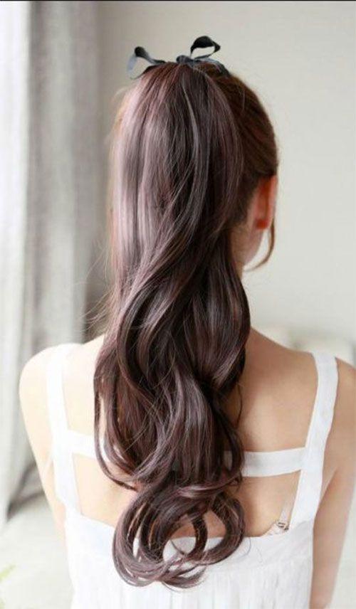 une queue de cheval longue, des boucles, un ruban dans les cheveux