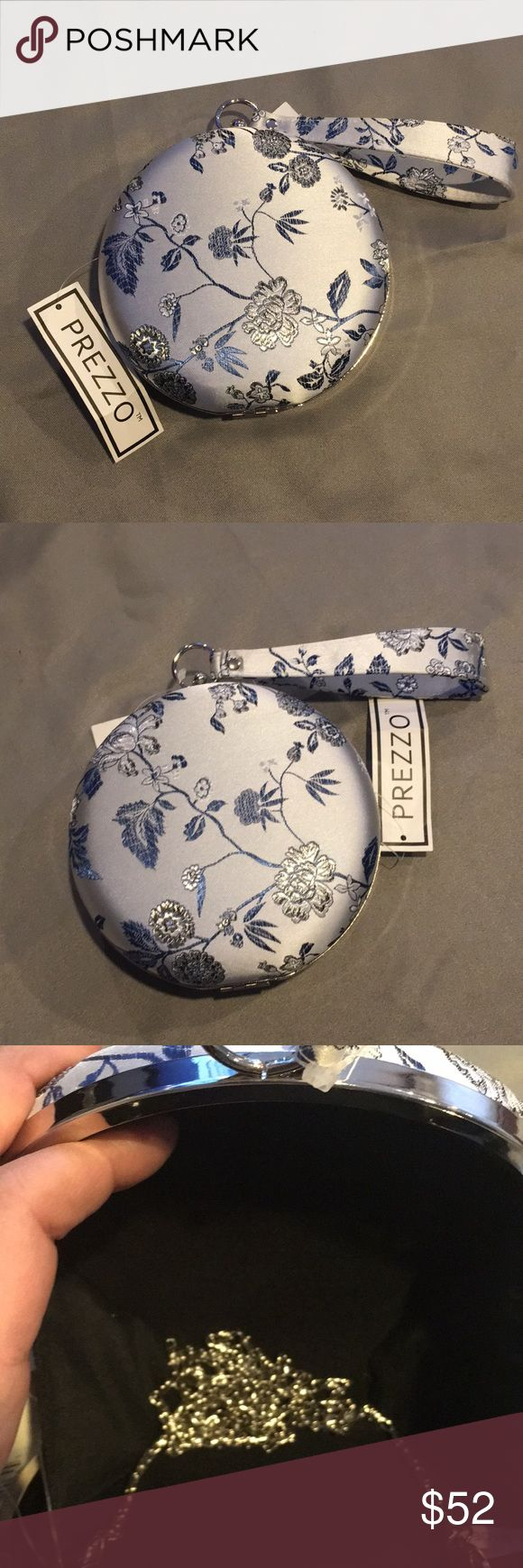NWT Prezzo Silver, Blue and White Round Purse NWT Prezzo Silver, Blue and White Round Purse. It's fabric with flowers embroidered on it. It can be used as a clutch or shoulder purse. The shoulder strap is removable. Measures approx 6 inches round. The clutch strap is approx 6 inches long and the shoulder strap has approx a 21 inch drop. Prezzo Bags Clutches & Wristlets