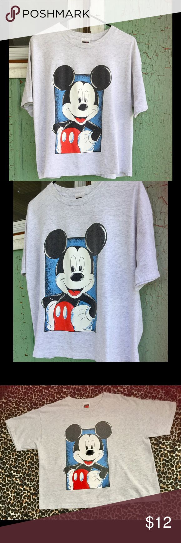 """Vintage 90s MICKEY MOUSE decal Retro T-shirt O/S Super KOOL Retro vintage 90s MICKEY MOUSE t-shirt by Mickey Unlimited. Super soft cotton pullover in light grey.  Cut is full. Giant Mickey decal on front. Would look cute over a beach bikini!  Size: Label says: One Size Fits Most (Fits XL)  Bust: up to 44"""" Waist: 46"""" across bottom Length: 12"""" from underarm to hem Label: Mickey Unlimited  Material: Cotton Vintage Condition: EX. No rips, stains or any flaws found. Vintage Tops Tees - Short…"""