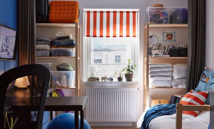 Bagvæggen af et kollegieværelse med reoler fyldt med sengetøj, makeup, rengøringsprodukter og tøj og et rød- og hvidstribet rullegardin for vinduet imellem de 2 reoler.