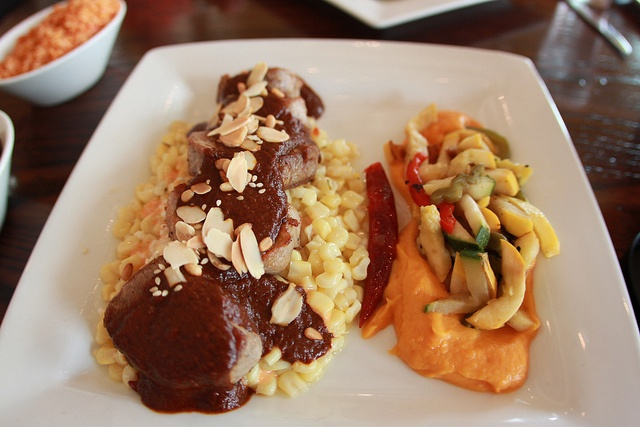 Puerco en Salsa de Mole Negro - Roasted pork tender loin with mole negro sauce, served with esquites (roasted corn), sweet potato mash, beans and vegetables. - $25.95