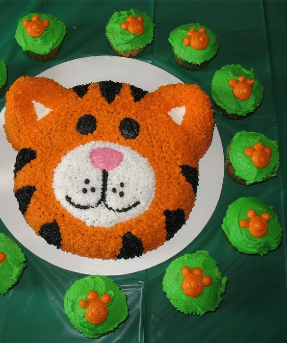 Tiger Cake    Little dollops of icing make a friendly orange tiger. Small cupcakes with paw prints finish off the fun presentation.