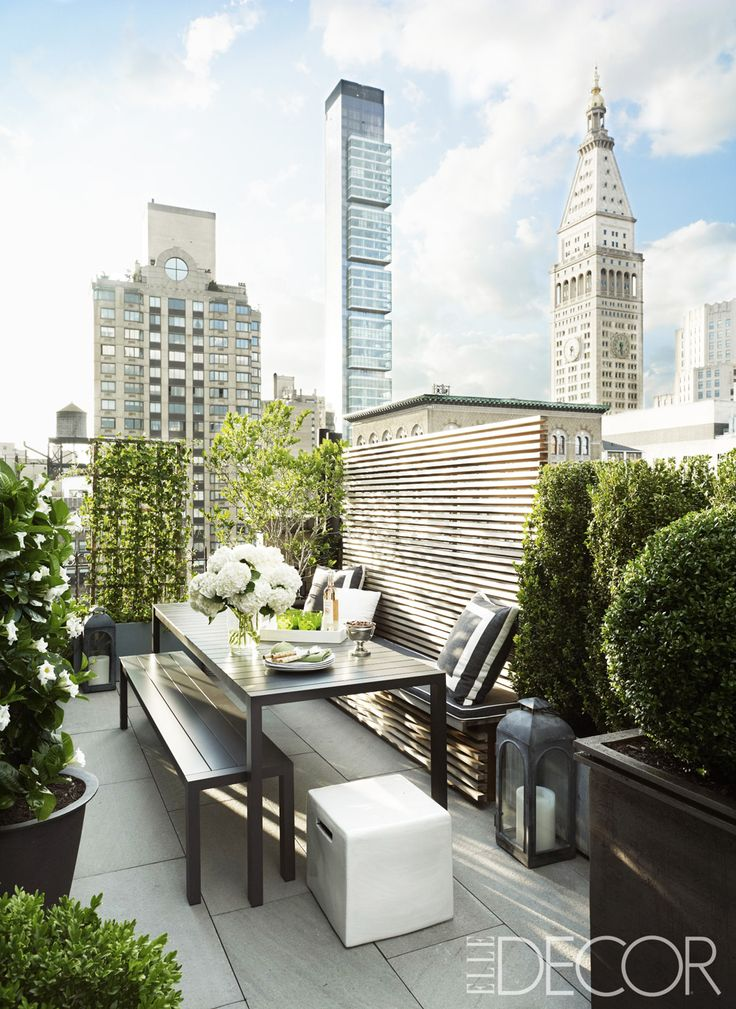A lush green terrace with dining and garden in a New York City penthouse apartment.
