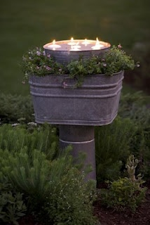stacked galvanized containers, middles is planted with flowers and top is filled with water and floating candles