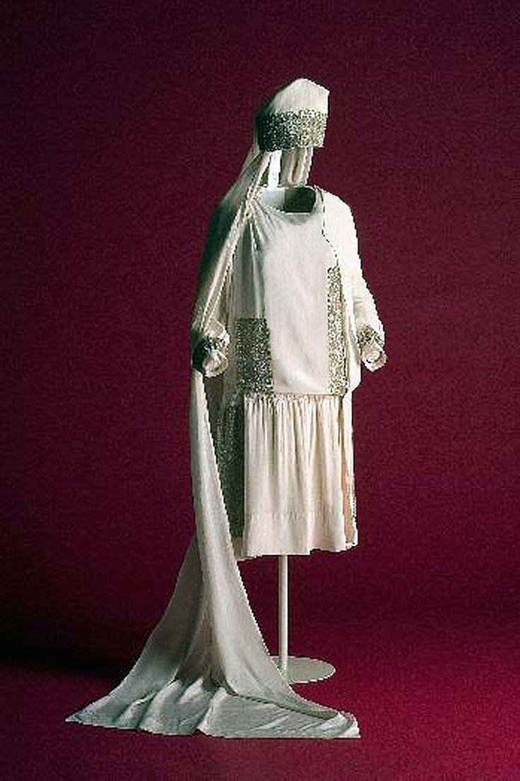 Wedding dress, 1925. Ecru silk crepe. Slit skirt shows underskirt of same fabric. Matching headdress & train. Museo del Traje, Madrid