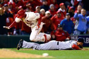 Allen Craig of the St. Louis Cardinals trips over Red Sox third baseman Will…