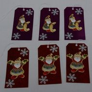 A pretty set of six handmade large Luggage style Christmas Gift Tags.  The set comprises of two different Santa images, three on the background of red holographic card and three backed onto a rich purple holographic card.  Those on the red background d...