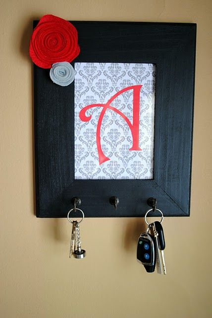 DIY Key Holder  1. Buy a cheap frame, scrapbook paper, and rosettes from hob lob. 2. Print initial on paper - just picked a font I liked on word 3. Buy hook screws at home depot 4. Glue on rosettes and hang  *or do this fancy one here :)
