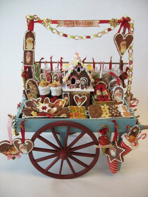 Peddlars cart filled with decorated gingerbread cookies, Christmas crackers, filled stockings, marzipan fruits, jars filled with festive candies, hanging sweet cones, and a gingerbread house. Carl Bronsdon