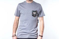 Camiseta de algodón marca Vans para hombre, de color gris, con bolsillo en el pecho estampado con un original y divertido diseño marca de la casa: bailarinas hawainas a ritmo de hula-daze ;)