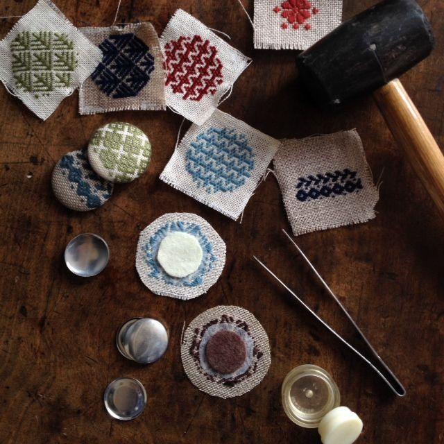 こぎん刺しが刺しあがった布で、クルミボタンを作ります 私なりの方法で作っていますので正解かどうか分かりませんが、出来上がりがきれいになるように試行錯誤しています まず、刺した布を押し洗い程度に洗います タオルに広げて水を切っている間に、接着芯とフェルトを丸く切り抜きます 切り終わる頃には、刺した布もいい具合に水気が切れているので、布も丸く切り抜きます 布に接着芯をアイロンで貼り付けます 接着芯は、クルミボタンのカーブをなだらかにする為に貼っています 出来上がった時に布目の隙間から、クルミボタンのアルミが光って見えてしまうのも防ぎます フェルト (または フェンネル)を挟んでから、クルミボタンの打ち具にセットして ぐいっと差し込みます 布に厚みがあるときはゴムの金槌を使って叩いて入れます フェルト(時にはフランネル)は、クルミボタンをふっくらさせる為に入れています 布の厚みで挟み込むフェルトの厚みを変えたり、角を落とす作業をしています 出来上がったクルミボタンの裏にピンを接着して、ブローチの出来上がりです
