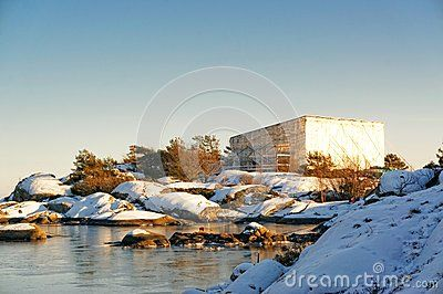 The high stage, tent covered with a protective foil. Securing the summer house built on a rocky island. Norwegian coast vegetation surrounds the gray cottage with a big green terrace. Around the spruces, pines, heathers in the winter coat. North Sea Coast. Skagerrak coastline. Norwegian winter landscape.