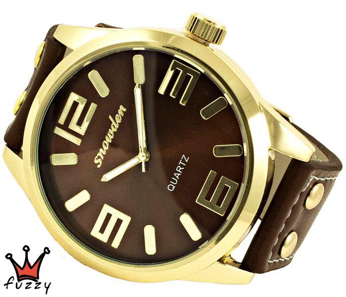 Γυναικείο ρολόι, σε χρυσό και καφέ, με μεγάλα νούμερα στο εσωτερικό του. Λουράκι δερματίνης σε καφέ χρώμα. Διάμετρος καντράν 50 mm.