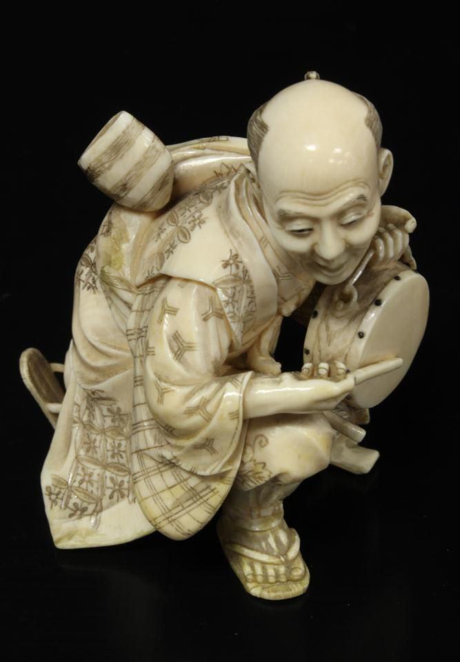 """JAPANESE HAND CARVED IVORY FIGURE OF MAN w DRUM Japanese ivory figure depicting a kneeling man playing a drum. Signed to bottom. Measures 9 1/8"""" height x 3 1/4"""" width (23.1cm x 8.2cm)."""